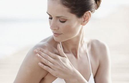 Žena nanášajúca krémový gél na rameno