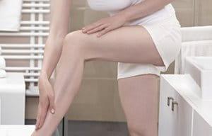 Žena aplikujúca krém na ľavú nohu